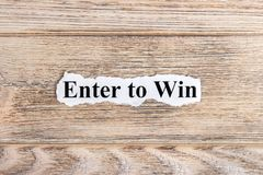 Enter to win text on paper. Word Enter to win on torn paper. Concept Image.  Stock Images