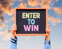 Enter To Win word on blackboard with hands are holding. Royalty Free Stock Photos