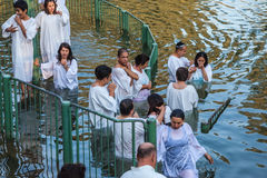 They enter the water, dressed in white robes Stock Images