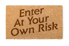 Enter At Your Own Risk Welcome Mat On White Stock Photography