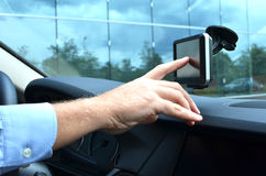 Entering an address into the navigation system. Driver entering an address into the navigation system Stock Photography