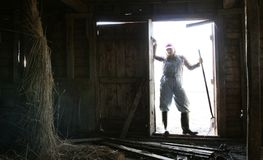 Entering dark barn. A girl in an overall standing in the doors to  a dark barn. High contrast  situation created due to bright light outside versus darkness Stock Photos
