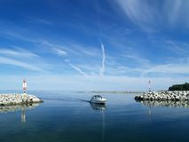 Entering Harbor. A power boat enters a still water harbor through a narrow opening in a breakwater stock photos