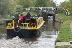 Entering Hirst Lock. A family steer their canal boat towards the open gates of Hirst Lock in Yorkshire watched by passers by stock photo