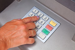 Entering personal identification number on ATM. Hand is entering personal identification number on ATM dial panel Stock Photos