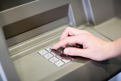 Entering PIN on an ATM stock image