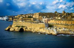 Entering the port of Valletta,Malta. Traditional stone made buildings and fotress in Valletta,Malta with a blue sky,clouds and coastline Stock Photo