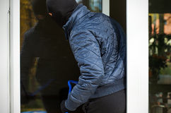 Entering though window. A burglar entering a house through an open window Royalty Free Stock Image