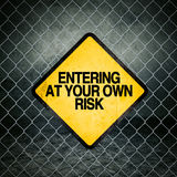Entering at Your Own Risk Grunge Yellow Warning Sign Stock Photo