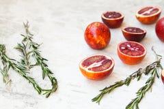Entero anaranjado siciliano rojo y corte en un fondo ligero con las ramas del romero Luz del día, espacio abierto para su texto Imagen de archivo libre de regalías