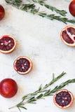 Entero anaranjado siciliano rojo y corte en un fondo ligero con las ramas del romero Luz del día, espacio abierto para su texto Fotos de archivo libres de regalías
