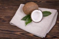 Entero y agrietado en medios cocos con las hojas verdes en una tela ligera y en una tabla de madera del marrón oscuro Frutas trop Imágenes de archivo libres de regalías