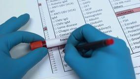 Enterovirus doktor som kontrollerar sjukdomen i labbmellanrumet som visar blodprövkopian i rör lager videofilmer