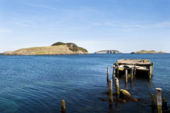 Enterprise Dock. Newfoundland Coastline in High Sun showing Destroyed Dock and Offshore Islands Stock Photo