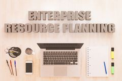 Enterprise Resource Planning. Text concept with notebook computer, smartphone, notebook and pens on wooden desktop. 3D render illustration Stock Images