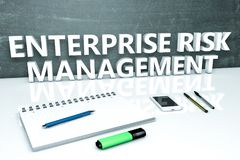 Enterprise Risk Management. Text concept with chalkboard, notebook, pens and mobile phone. 3D render illustration Royalty Free Stock Photo