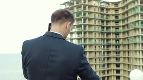 Enterprising architect talking on the phone while standing next to new building stock video footage