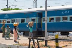 Enterprising Indian traders on the railway. Karnataka, India - March 2, 2018: Hawkers gathered on the platform at Shrirangapattan railway station after selling Stock Images