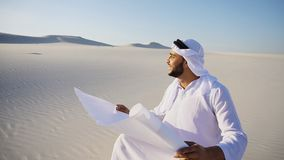 Enterprising male sheikh businessman sitting with white paper in. Educated Muslim Arabian UAE Sheikh entrepreneur and designer reads project of future Stock Photography
