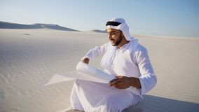 Enterprising male sheikh businessman sitting with white paper in. Educated Muslim Arabian UAE Sheikh entrepreneur and designer reads project of future Royalty Free Stock Images