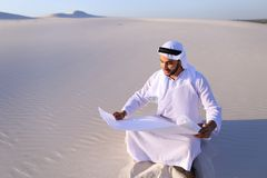 Enterprising male sheikh businessman sitting with white paper in. Educated Muslim guy entrepreneur and designer reads project of future construction, comes up Stock Images