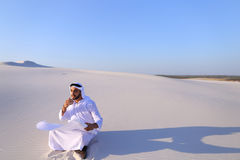 Enterprising male sheikh businessman sitting with white paper in. Educated Muslim guy entrepreneur and designer reads project of future construction, comes up Royalty Free Stock Images