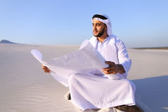 Enterprising male sheikh businessman sitting with white paper in. Educated Muslim guy entrepreneur and designer reads project of future construction, comes up Stock Image