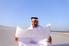 Enterprising male sheikh businessman sitting with white paper in. Educated Muslim guy entrepreneur and designer reads project of future construction, comes up Stock Photo