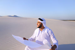 Enterprising male sheikh businessman sitting with white paper in. Educated Muslim guy entrepreneur and designer reads project of future construction, comes up Stock Photography
