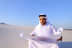 Enterprising male sheikh businessman sitting with white paper in. Educated Muslim guy entrepreneur and designer reads project of future construction, comes up Royalty Free Stock Photos