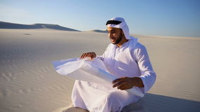 Enterprising male sheikh businessman sitting with white paper in hands and thinking of ideas for new project in desert. Educated Muslim Arabian UAE Sheikh stock video