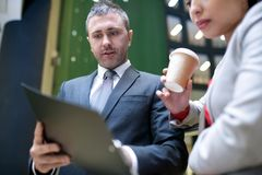 Enterprising manager showing his business plan. Confident handsome young male business specialist with stubble showing clipboard with papers to lady boss while Stock Image