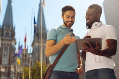 Enterprising remarkable guy showing his friend something. Stunning idea. Lively energetic ambitious men meeting his colleague and sharing a concept of the new Royalty Free Stock Photo