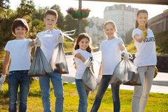 Enterprising volunteers being proud of done task. Follow us. Young team making goodness for humanity and smiling after cleaning park Royalty Free Stock Images