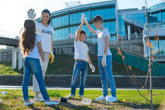 Enterprising young volunteers being proud. Follow us. Young team being proud for making goodness for humanity, smiling after cleaning park Stock Image