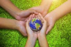 Enterre o planeta no fundo asiático da grama verde da mão das crianças Fotos de Stock Royalty Free