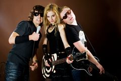 Entertaiment. Rock band playing in photostudio on brown background Stock Photo