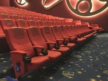 Entertaiment. View of interior cinema hall with rows of red seat in low light condition before the movie starts Stock Photography