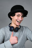 Entertainer. Cute teenager boy with hat and earphones on a gray background royalty free stock photography
