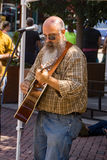 Entertainer at a Farmers Market. Roanoke, VA – August 19th: Entertainer playing a guitar and singing at Center in the Square located in downtown Roanoke Stock Images