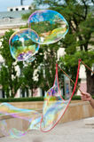 Entertainer making bubbles. Hand of street entertainer making large bubbles with trees in background; urban scene stock photography