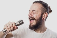 The entertainer. Young  talking man holding microphone, Isolated on white background. Studio shot Royalty Free Stock Image