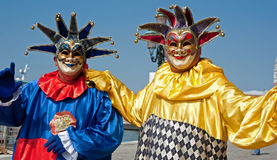 Entertainers in Venice. Pavement entertainers with Venetian face masks beside the Venice Lagoon stock photo
