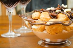 Entertaining. Bowl of profiteroles with glasses of red wine on a dining table Stock Image