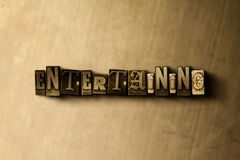 ENTERTAINING - close-up of grungy vintage typeset word on metal backdrop Stock Images