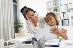 Entertaining daughter. Business women trying to entertain her daughter with digital tablet Royalty Free Stock Photos