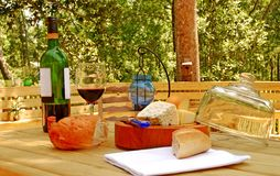 Entertaining on Deck. Pretty array of rustic bread, cheese, and red wine on outdoor deck Royalty Free Stock Photos