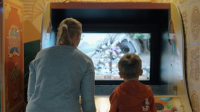 Entertainment in amusement park. MOSCOW, RUSSIA - SEPTEMBER 10, 2016: Child and mother having fun in amusement park Cosmic. They playing with on arcade machine stock video footage