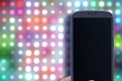Entertainment App. Smatrphone and disco background. Idea for party app, digital detox, taking shots, accessing apps, Internet, blogs and others. The background Stock Image