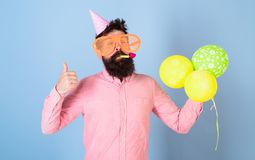 Entertainment artist at kids party, International children day celebration. Bearded man with huge glasses, wistle and. Balloons, fun concept. Hipster with Stock Image